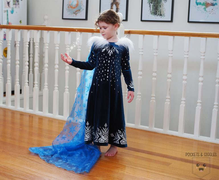 Image of a child in an Elsa costume. Magic comes from her extended hand.