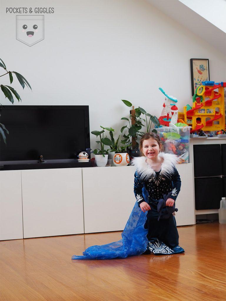 A girl in an Elsa dress runs forward, giggling.