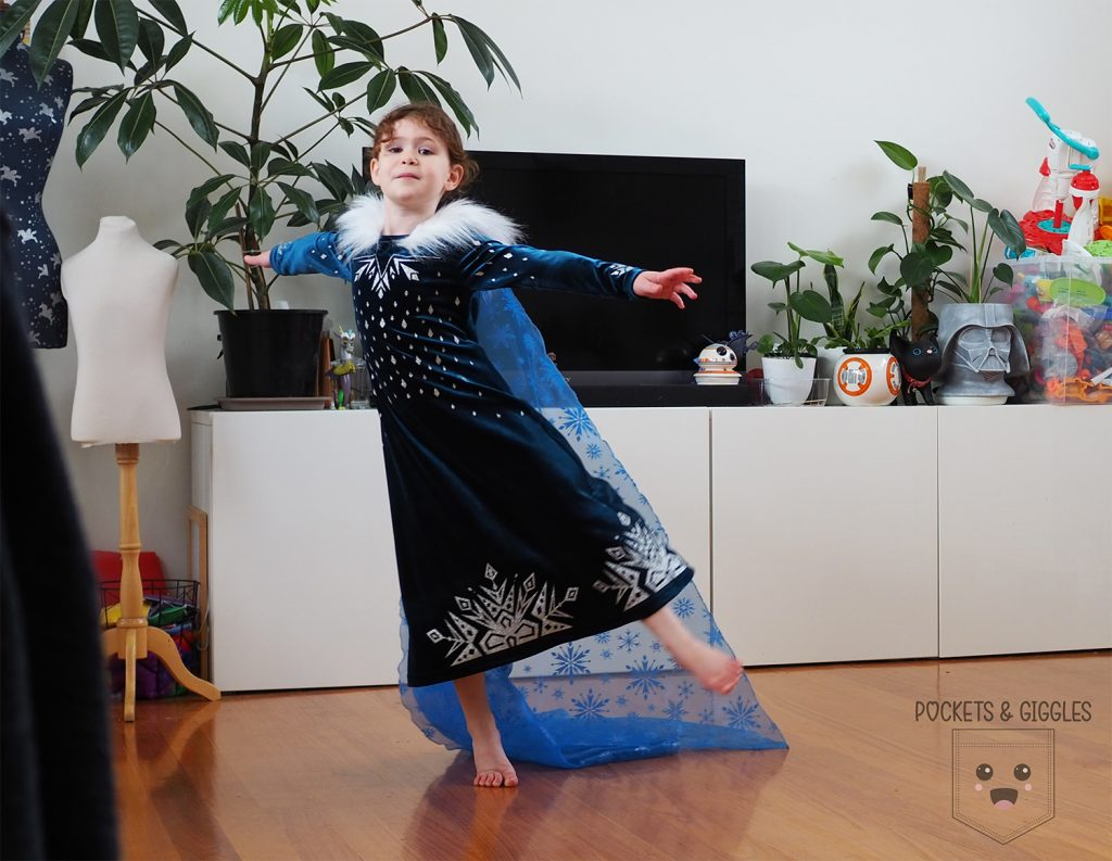 Image of a girl dancing in an Elsa dress.