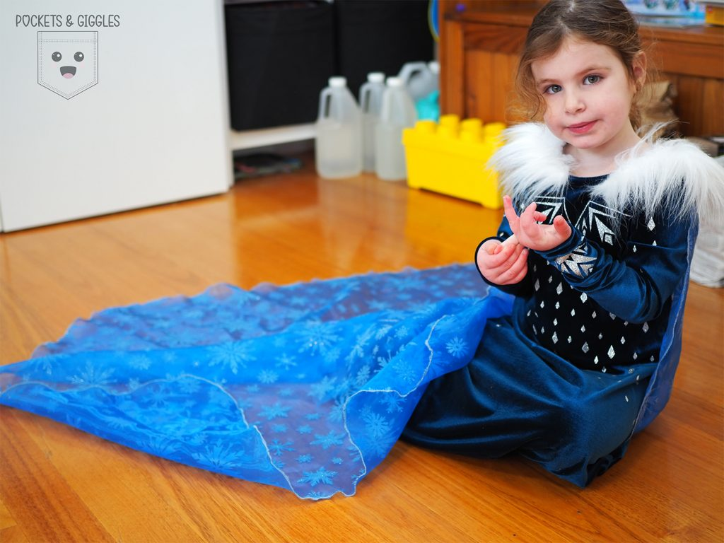 A little girl wearing an Elsa dress, playing with her hands.