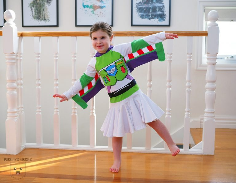 A girl in a Buzz Lighyear dress, with wings outstretched