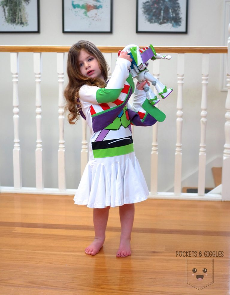 Girl in a Buzz dress holding up a Buzz toy.