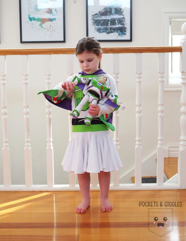 Girl wearing a Buzz dress holding a Buzz toy.