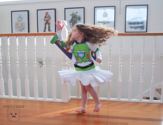 Girl in a Buzz Lightyear dress spinning.